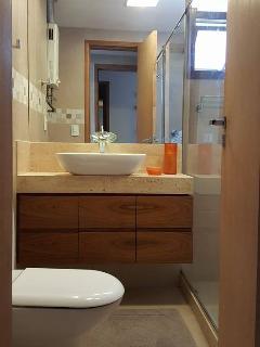 Banheiro da suíte com cuba apoiada sobre armário 2 portas com 2 gaveteiros, ambos com amortecedores.