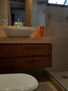Visão do banheiro da suíte com detalhes para o box em vidro temperado e janela de ventilação.