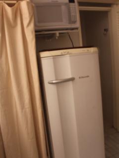 área de serviço com microondas, geladeira e maquina de lavar roupa