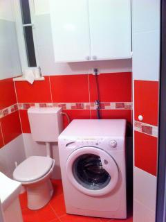 Bathroom #2 with toilet and washing machine.