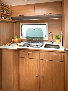 Practical kitchen area with hob, sink and oven