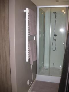 Salle de bain avec douche, radiateur sèche-serviette, WC et lavabo.  Serviettes fournies