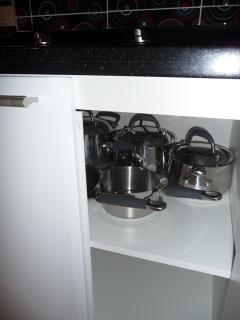 Cupboard in kitchen opened under electric cooking plates with various cooking pans