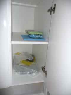 Cupboard in kitchen opened with various cleaning material for kitchen