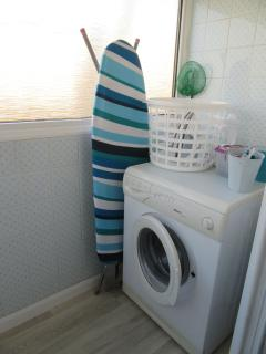Utility room with washing machine, iron and ironing board and folding dryer