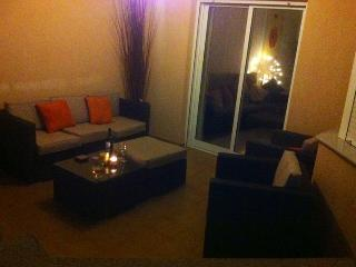 Terrace area at front of apartment with modern wicker furniture. Pool a few metres away