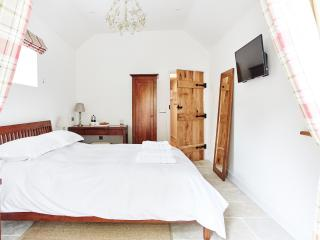 The bedroom has a vaulted ceiling with chandelier.