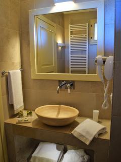 Bagno con lavabo in pietra, asciugacapelli e ampia doccia