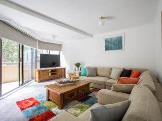 Spacious living area with 60' TV and private balcony in this large four bedroom Melbourne apartment