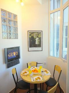 Eat-in kitchen alcove with bay window and one of two LCD televisions with cable