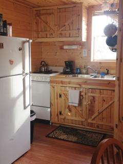 Kitchen with refrigerator, stove, microwave, coffee pot. Stocked with common pantry items.