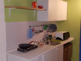 anglolo cottura dotato di fornetto, frigo, piano di cottura, pentole, bicchieri, posate ecc