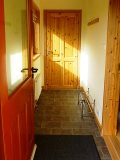Entrance hallway leading to kitchen.  Washing machine and oil central heating boiler in cupboard.
