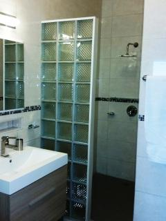 2nd bedroom ensuite bathroom with large square head rainshower, lots of cabinet storage