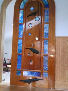 Stained glass custom bathroom door with whale carvings.