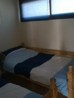 Twin bedroom, two single beds, a wardrobe with extra sheets and pillows etc. A portable fan .