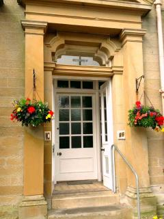 The front door with hanging baskets during summer months!