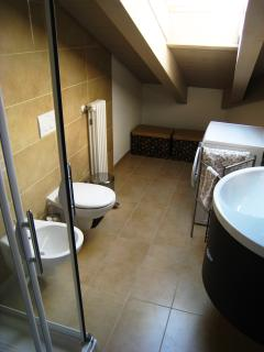 Main bathroom adjacent to the upstairs bedrooms with skylight and washing machine