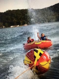 Danielle and Russell tubing behind Grandpa Mark.