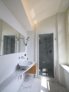 Bagno con finiture in marmo e stucco veneziano.