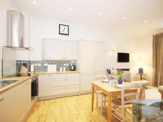 Large, light, modern kitchen adjacent to lounge area. Dishwasher, washing machine, halogen hob.