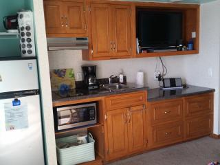 Kitchenette with fridge, microwave and cooktop. Fully stocked with cooking & eating needs.