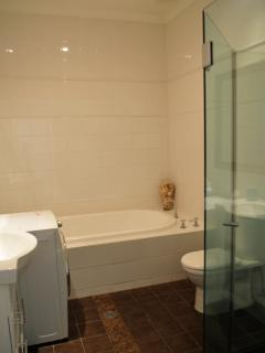 Full bathroom with oversize tub, shower and combined washing machine/dryer