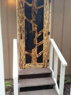 Hand carved bear screen door entrance to the cabin with two half steps. No other steps