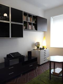 Hermoso salón con amplio sofá, tres butacas, elegante mobiliario y zona de librería.