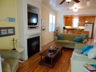 Curl up in the comfortable living room with wood floors, surround sound, flat screen TV & fireplace