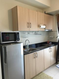 Half kitchen with sink, fridge and microwave.