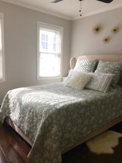 The 1st bedroom includes a queen sized mattress and the sun filled room faces the front of the house