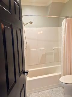 Full tub and shower in upstairs bathroom with removable, handheld shower nozzle and shower amenities