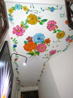 The front hallway ceiling features a mural of Mexican flowers welcoming you.