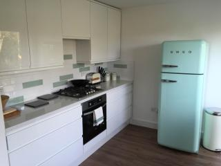 Newly fitted kitchen with premium appliances opening to patio
