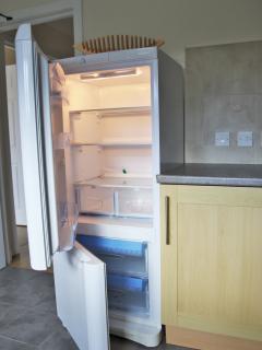 Kitchen with under-plinth heating, fridge/freezer, dishwasher, washing machine, oven & gas hob.
