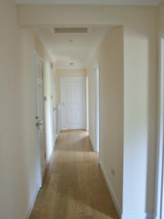 Hallway from the entrance towards the kitchen, single room, twin room, bathroom & living room doors.
