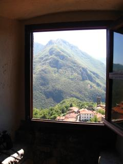 View from bedroom window looking onto village and mountains.