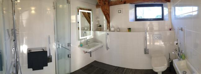Wet room designed by Motionspot. Removable shower seat, underfloor heating, large heated towel rail.