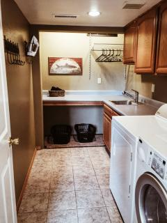 Full laundry room with front-loading washer & dryer, ironing board, iron, and large folding counter.