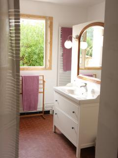 A big bathroom between the two bedrooms, with a shower, a toilet and a window.