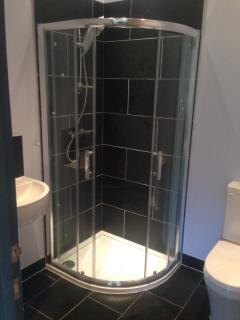 Bathroom with shower, WC, sink and towel heater