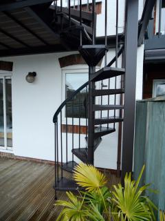 Spiral staircase leading from balcony to the deck.