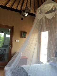 Lumbung suite queen bed with mosquito net, fan and views to the pol and garden.