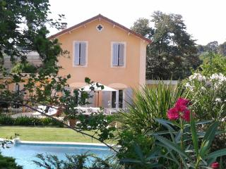 La maison vue du jardin derrière la piscine