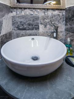 Bathroom sink surrounded by marble tiles.