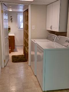 BATHROOM WITH TUB AND SHOWER COMBINATION AND FULL SIZE WASHER AND DRYER