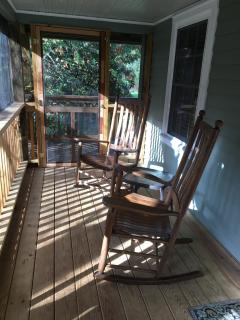 Screened portion of wrap-around porch includes comfy rocking chairs