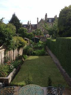 Rear Garden - lush green lawn, close clipped privet hedge leading onto vegetable garden and vinery.