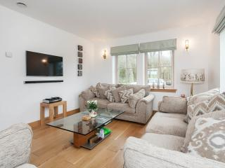 Open plan living space with large flat screen television with sound bar and full Sky Sports package